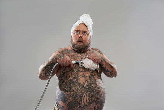 Fat shirtless man taking shower and looking surprised