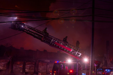 Unrecognizable Firefighters coming down the ladder