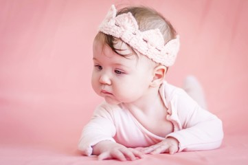 Sweet adorable six months old Caucasian baby girl with a pink cloth crown on a pink background. Infant girl revealing the world and learning to turn and crawl concept image.