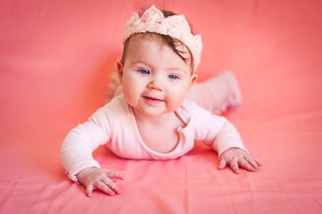 Sweet adorable six months old Caucasian baby girl with a pink cloth crown on a pink background. Infant girl smiling image.