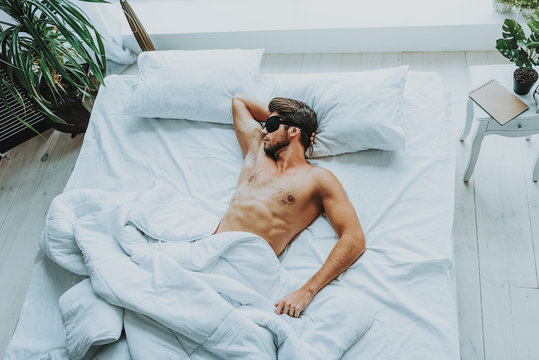Young attractive man sleep with blindfold in bed