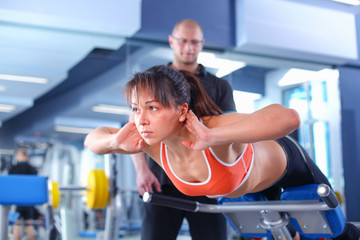 Beautiful woman at the gym exercising with her trainer . Beautiful woman.