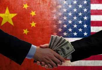 Two men/politicians in suits holding money/US Dollars and shaking hands with the national flag on the background - China and United States