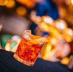 Negroni cocktail served freshly prepared on bar counter top in night club background