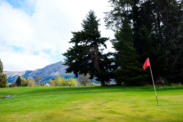 Red flag on golf green in Glenorchy, South Island, New Zealand