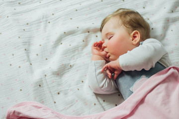 Infant baby sleeping and sucking thumb on white sheets
