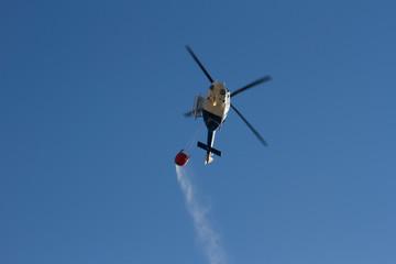Helicóptero de extinción de fuegos de montes, dirigiendose a un fuego derramando agua de una canasta que transporta.