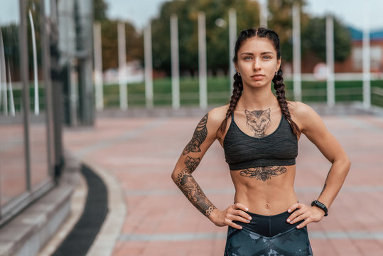 Girl athlete, summer city. Resting after playing sports on the street. In leggings and swimsuit. Woman with tattoos. Free space for text. Confident look. Emotions of a strong and confident person.