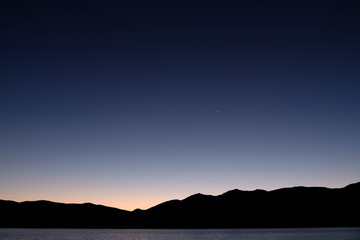Night view with silhouetted mountains and stars at Lake Te Anau, South Island New Zealand