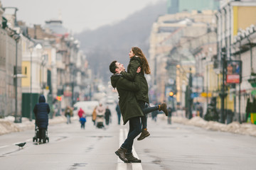 Young carefree happy people. Caucasian young students. Guy and girl. Love. Walk together on the european street in winter road. Theme love and happiness at a young age