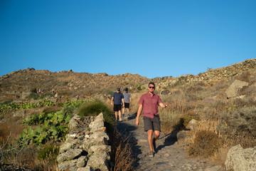 Friends go on a sunset hike in Santorini, Greece