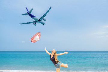 Woman have fun on the beach watching the landing planes. Traveling on an airplane concept