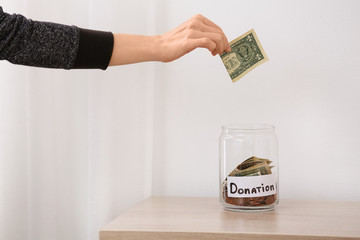 Woman putting money into jar with label DONATION on table against light background, closeup