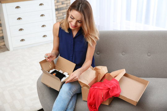 Young woman opening parcel on sofa in living room