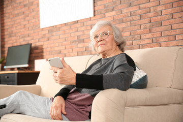 Elderly woman using smartphone on sofa in living room