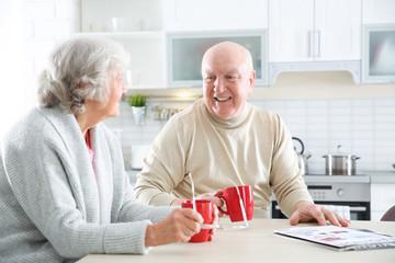Elderly couple drinking tea at table in kitchen