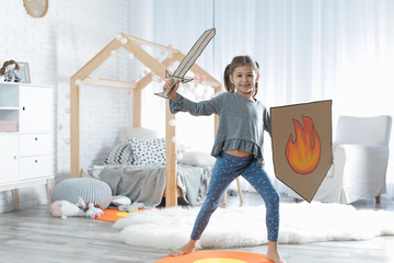Cute little girl playing with cardboard armor in bedroom