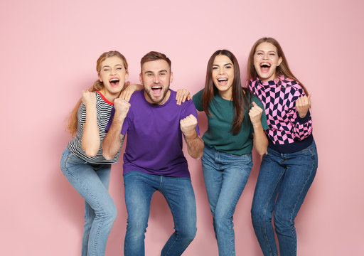 Young people celebrating victory on color background