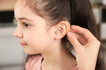 Young woman putting hearing aid in daughter's ear indoors, closeup