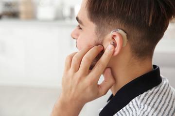 Young man adjusting hearing aid at home, closeup