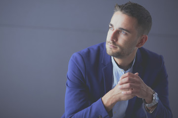 Young businessman sitting isolated on grey background.