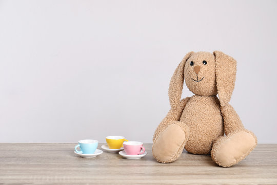 Adorable plush bunny and toy tableware on table against light background, space for text. Child room elements