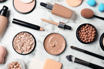 Flat lay composition with skin foundation, powder and beauty accessories on marble background