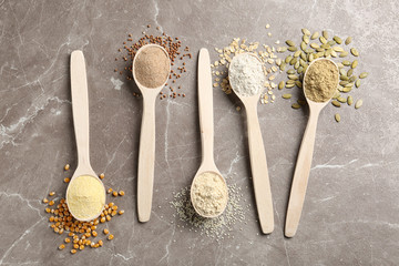 Spoons with different types of flour and ingredients on table, top view