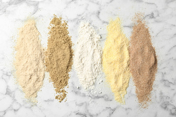 Stripes of different flour types on marble background, top view