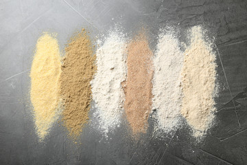 Stripes of different flour types on grey table, top view