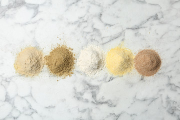 Piles of different flour types on marble table, top view