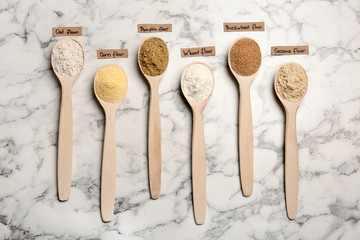 Spoons with different types of flour and tags on marble background, top view