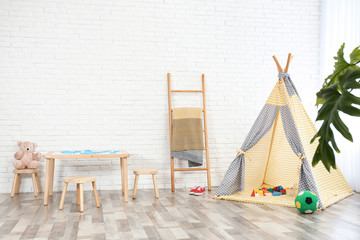 Cozy kids room interior with table, stools and play tent