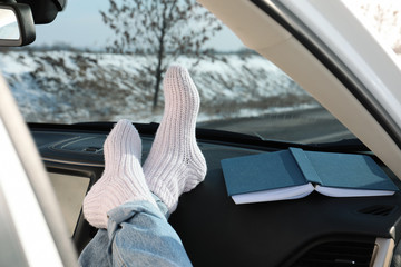 Young woman in warm socks holding her legs on car dashboard. Cozy atmosphere