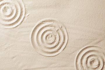 Zen garden pattern on sand as background, top view. Meditation and harmony