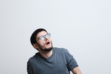 Portrait of shocked man looking up, over white background.
