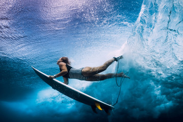 Surfer woman with surfboard dive under wave