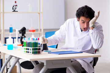 Young handsome chemist working in the lab