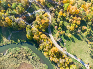 aerial top view of park in autumn. park scene image with yellow trees, asphalt sidewalks and river