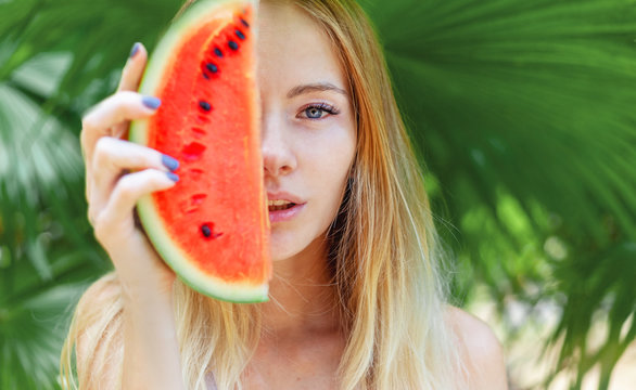 Beautiful young sensual sexy blonde with a slice of red watermelon in palm leaves, beauty and fashion, ecology and nature.