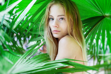 Beautiful young sensual sexy blonde  cool woman  in palm leaves, beauty and fashion, ecology and nature.