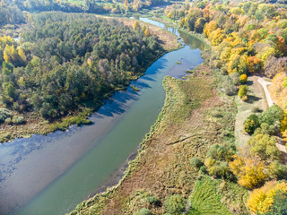 park landscape aerial top view. trees with gold autumnal foliage growing near cold river