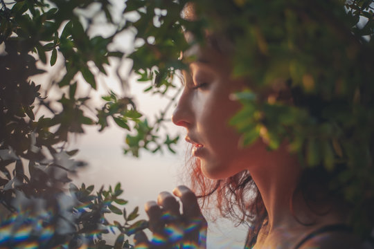 Portrait of a beautiful young woman with dark hair in a frame of branches and green leaves, summer and spring sensual portrait, natural beauty