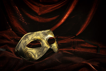 Photo of elegant and delicate gold venetian mask over dark velvet and silk background.