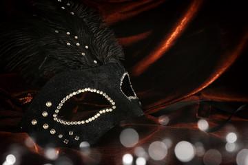 Photo of elegant and delicate black venetian mask over dark velvet and silk background.