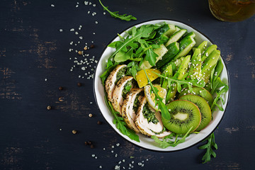 Buddha bowl dish with chicken fillet, avocado, cucumber, fresh arugula salad and sesame. Detox and healthy keto diet bowl concept. Overhead, top view, flat lay, copy space