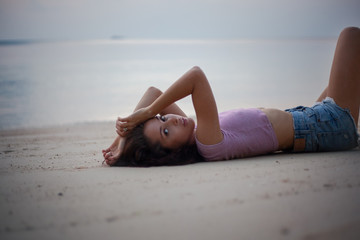 Young beautiful slim sensual woman lying on the sand on the beach, beauty and fashion, leisure and travel concept