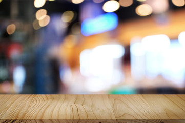 empty wooden tabletop over blur hypermarket background.