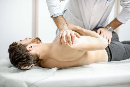 Professional senior physiotherapist doing manual treatment to a man in the cabinet of rehabilitation clinic
