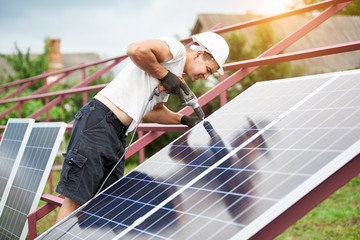 Back view of young technician in helmet connecting solar photo voltaic panel to metal platform using electrical screwdriver on bright sunny summer day.Stand-alone solar panel system installation.